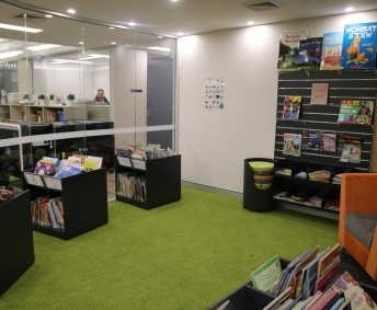 JUNIOR SCHOOL PICTURE BOOKS: Beautiful area at the front of the library, suitable for class reading. Seating pads for students, and teachers reading chair.